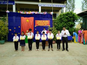 Ông Đoàn Văn Tuấn phát thưởng cho các hs đạt thành tích phong trào trong năm